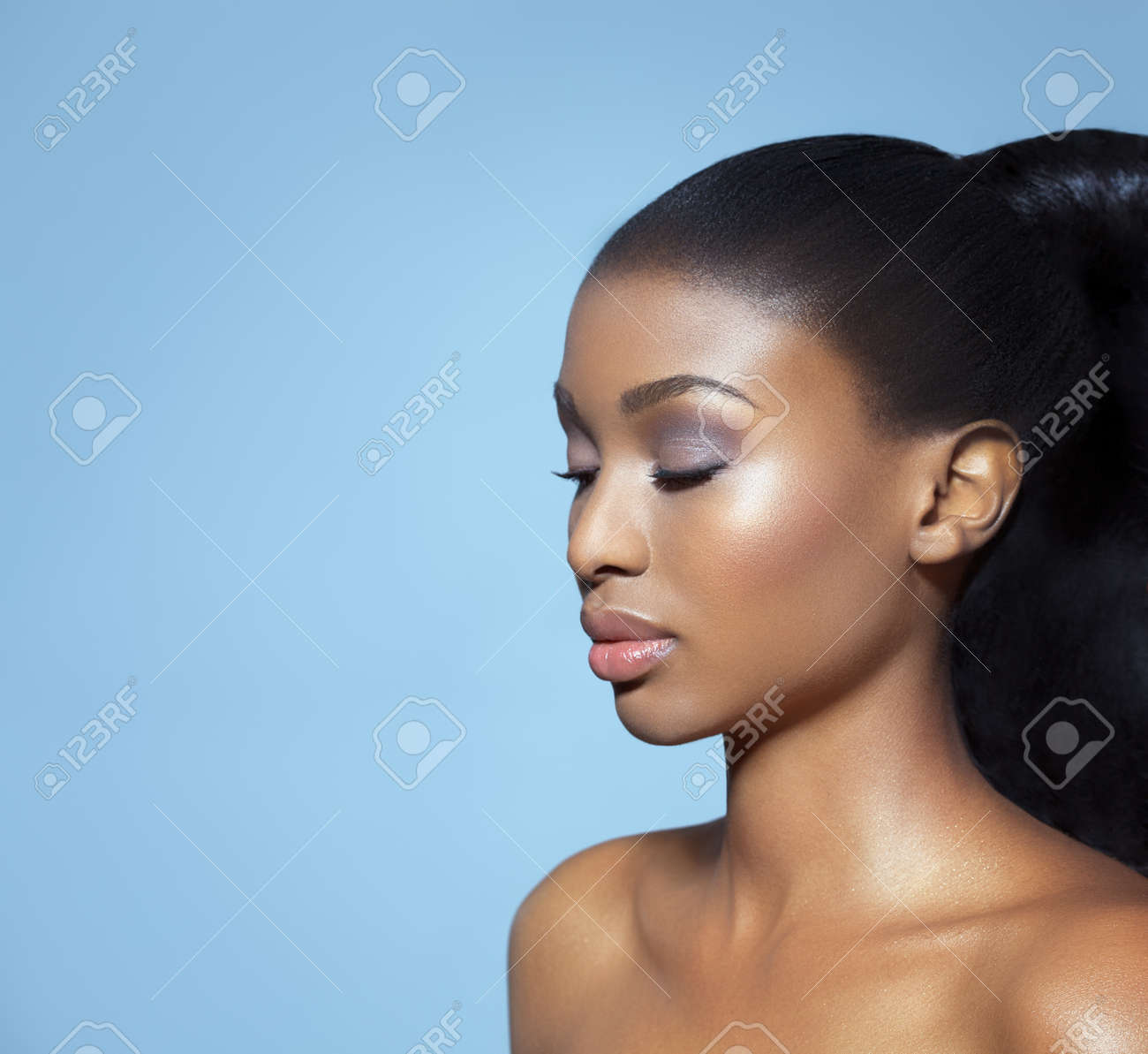 Portrait of beautiful serene African girl with closed eyes over blue studio background. African beauty with makeup and long hair. - 45872972