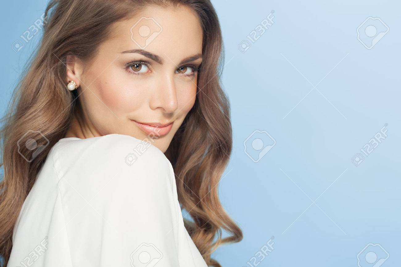 Young beautiful woman with long hair posing and smiling over blue background. Fashion and beauty concept in studio. - 51033458