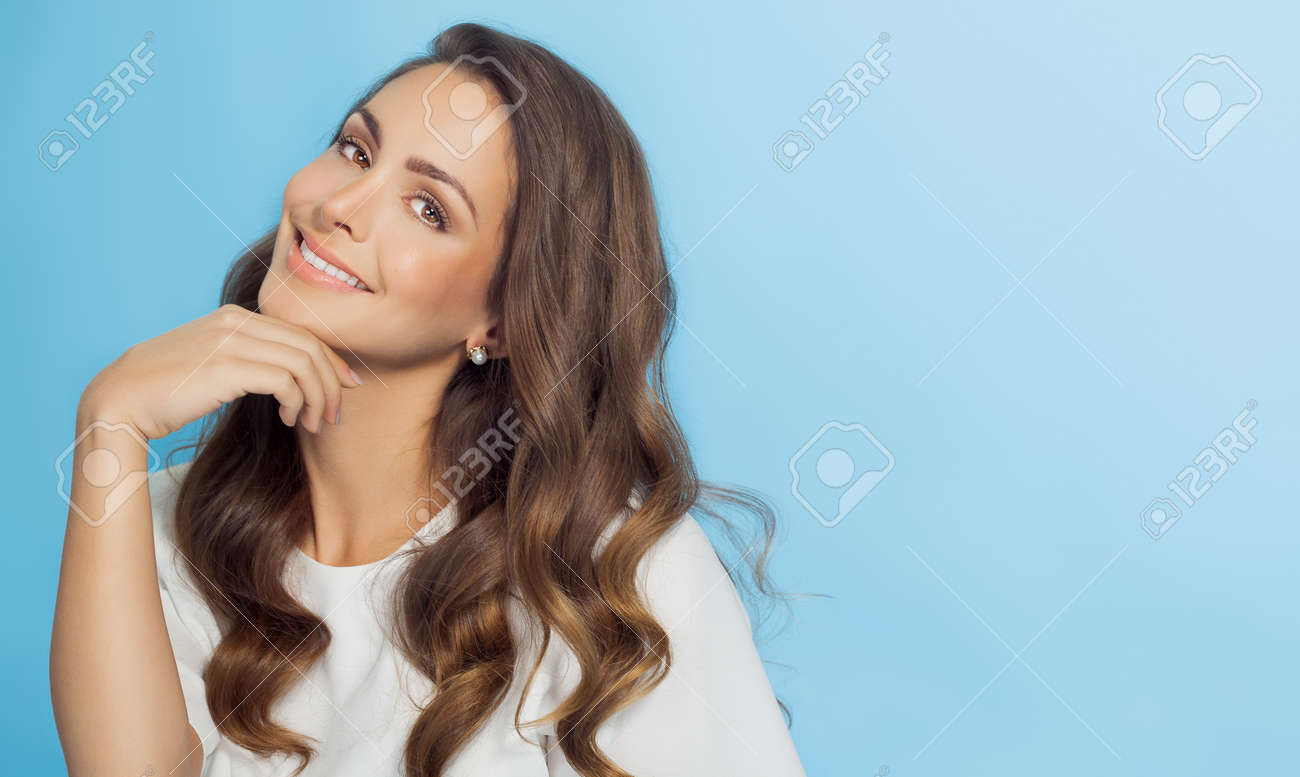 Smiling woman with long hair over light blue background. Fashion and beauty concept in studio. - 52219021