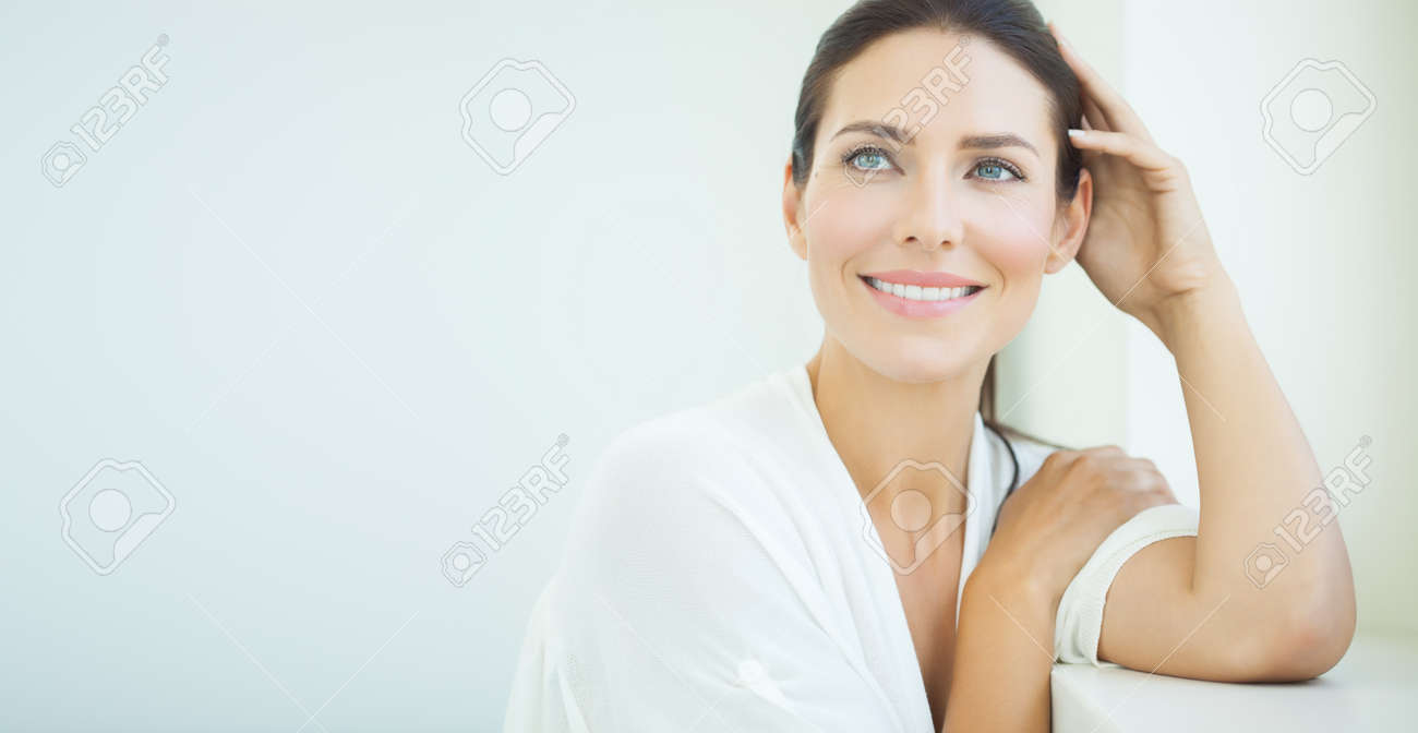 Beautiful woman sitting at window. Light blue and white day light and high key. - 59851544