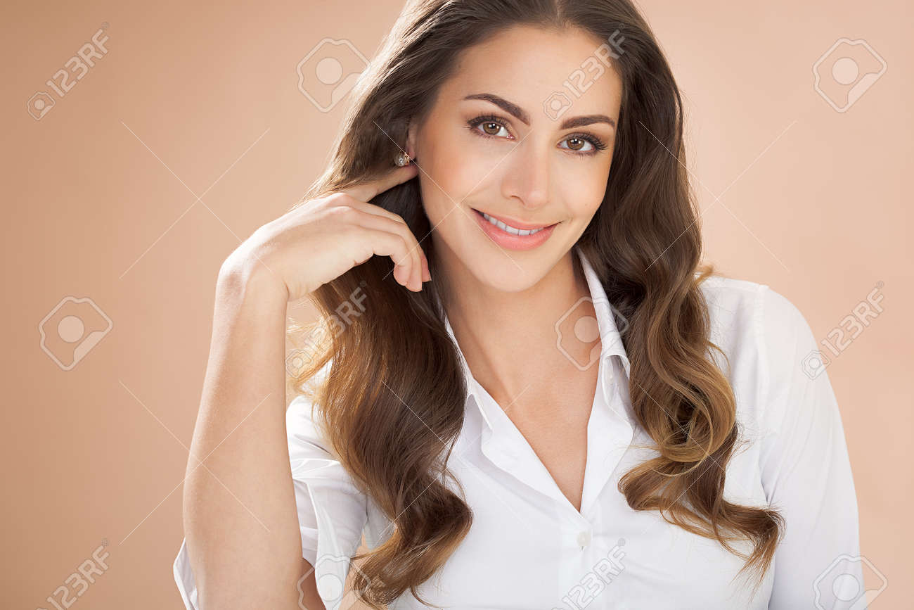 Smiling woman with long brown hair on beige background. - 59851554