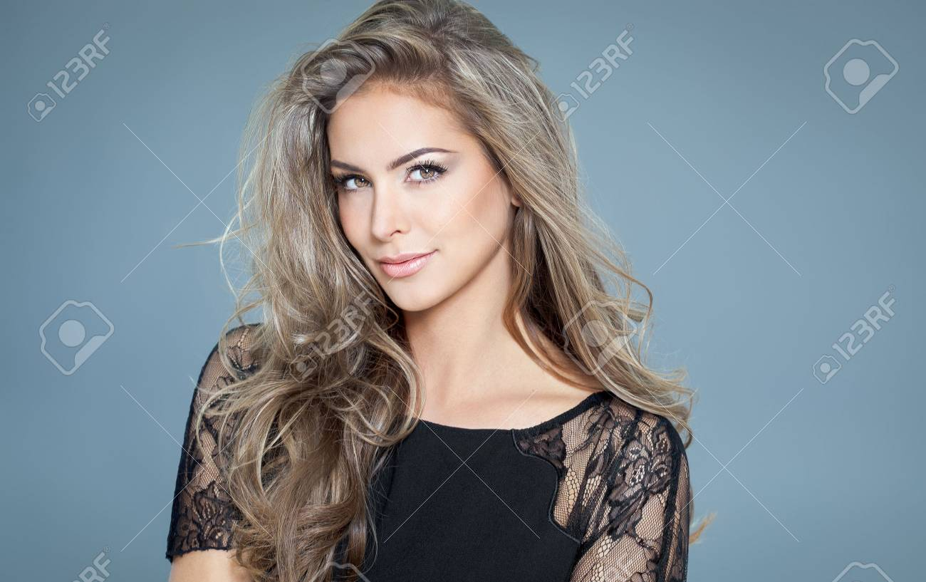 Young beautiful woman with long hair and highlights posing in black silk lace top. Smiling fashionable woman. - 65056686
