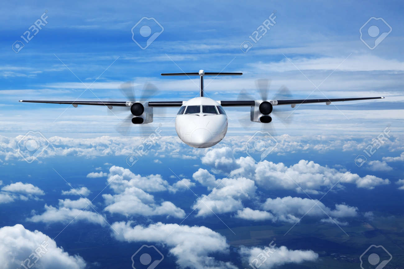 A passenger plane flying high in the sky above the clouds, close up, front view Stock Photo - 11729908