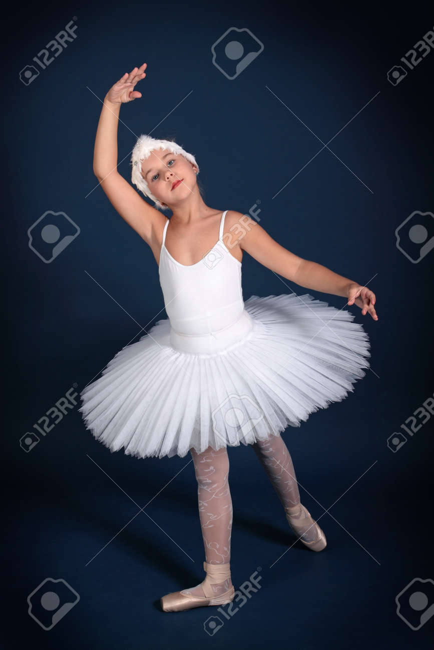 The ten years' girl dances in a ballet tutu on a dark blue background Stock Photo - 25558959