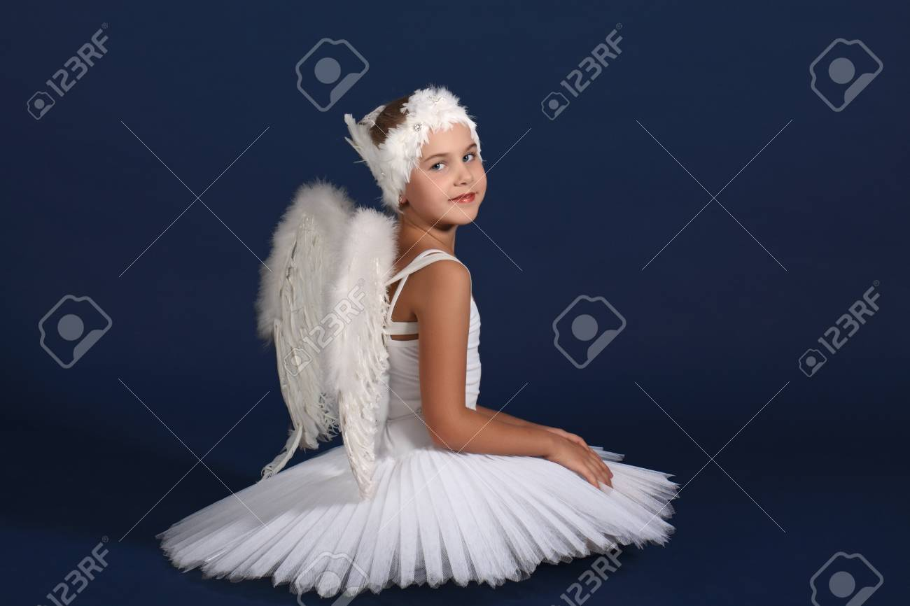 The ten years' girl sits in a ballet tutu on a dark blue background Stock Photo - 25558974
