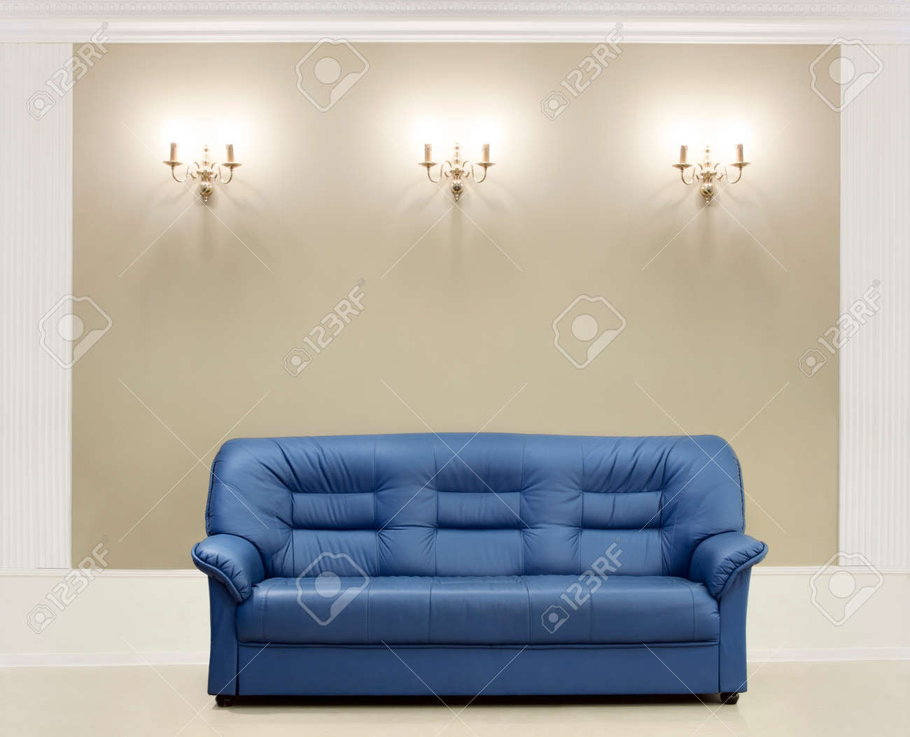 The dark blue leather sofa, is put about a wall with candelabrums