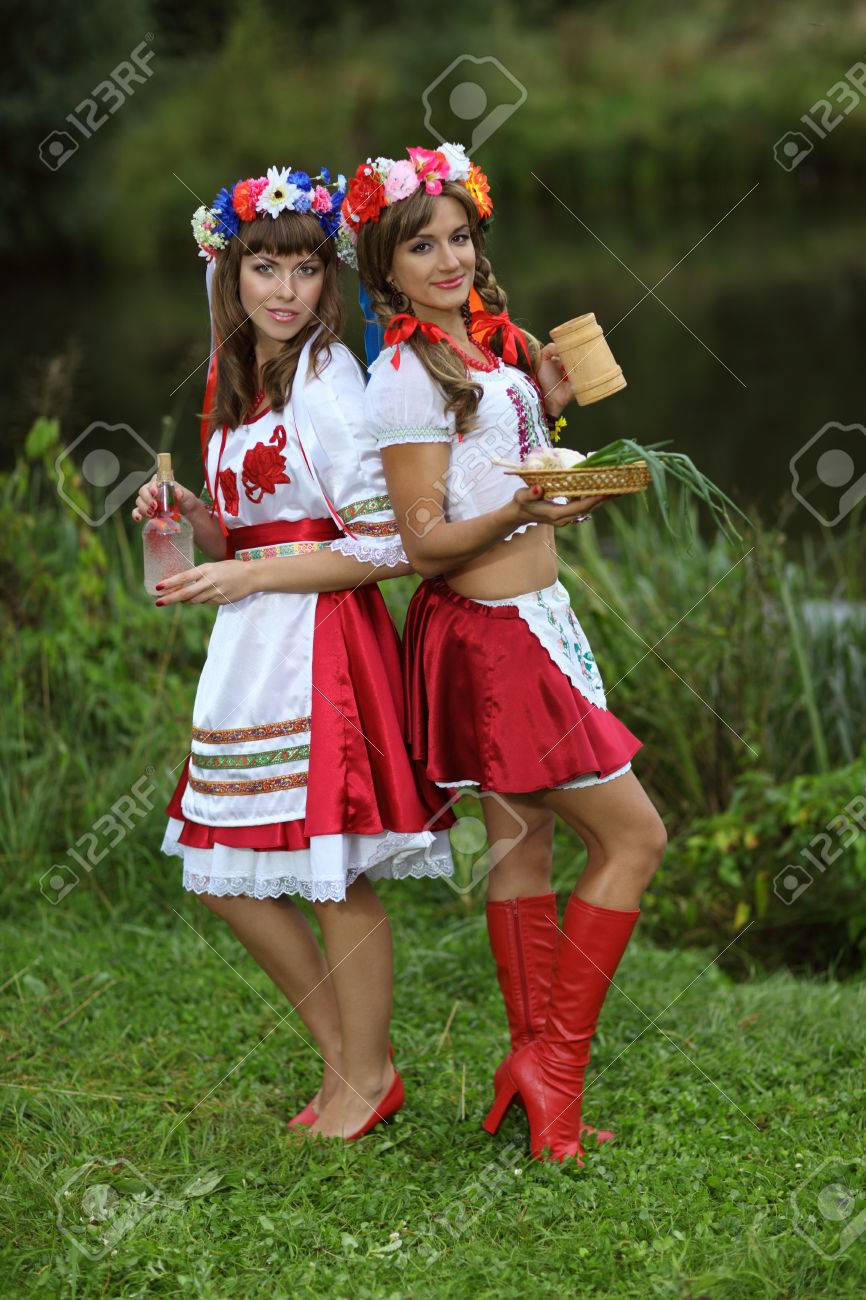 Two Girls In Ukrainian Costumes On The Banks Of The River With