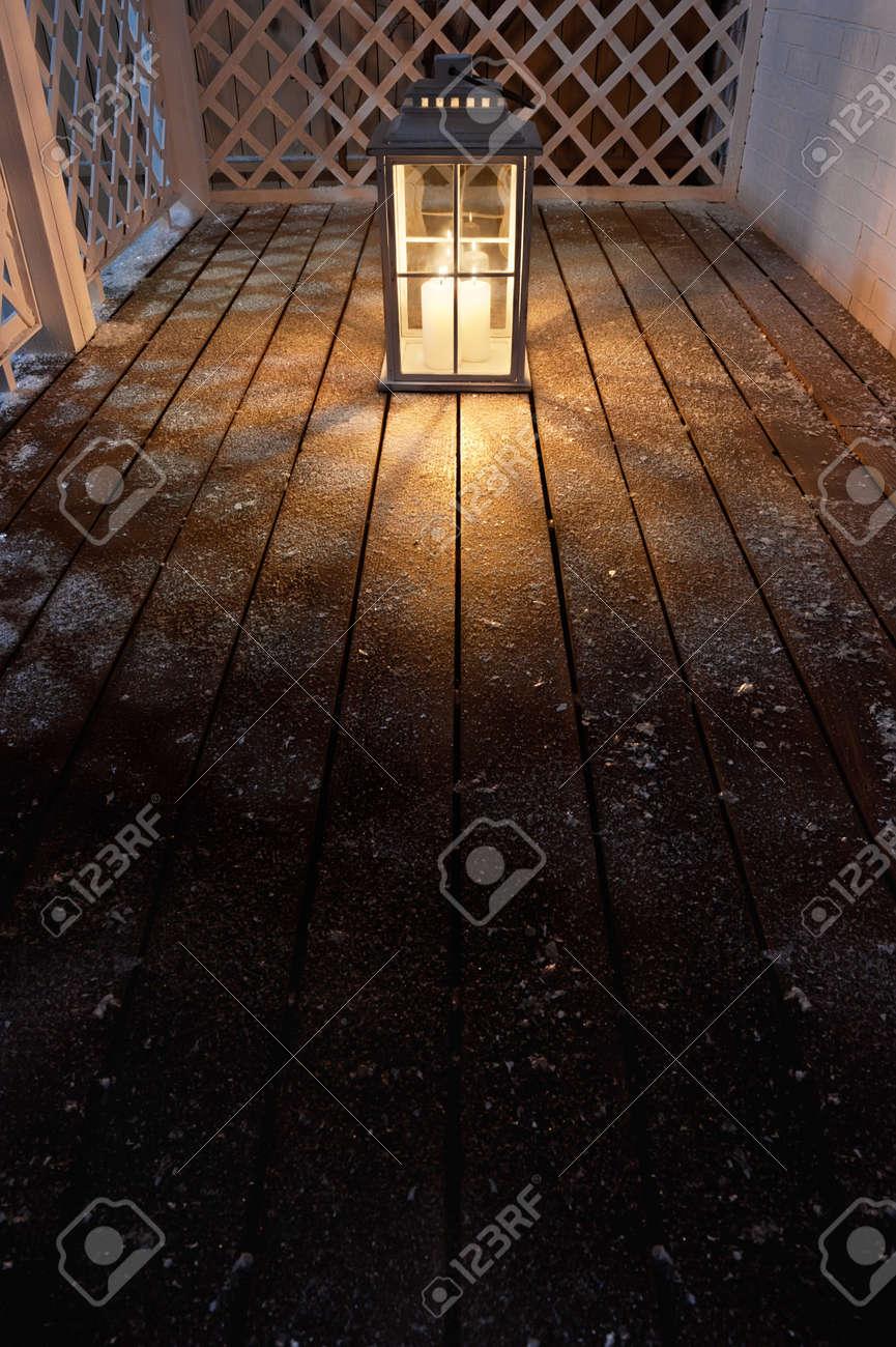 Lampe de jardin avec des bougies allumées dans la nuit d\'hiver neigeux