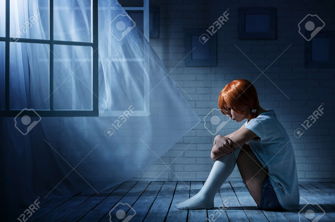 Lonely Girl Sits In An Empty Dark Room Opposite The Window Stock Photo