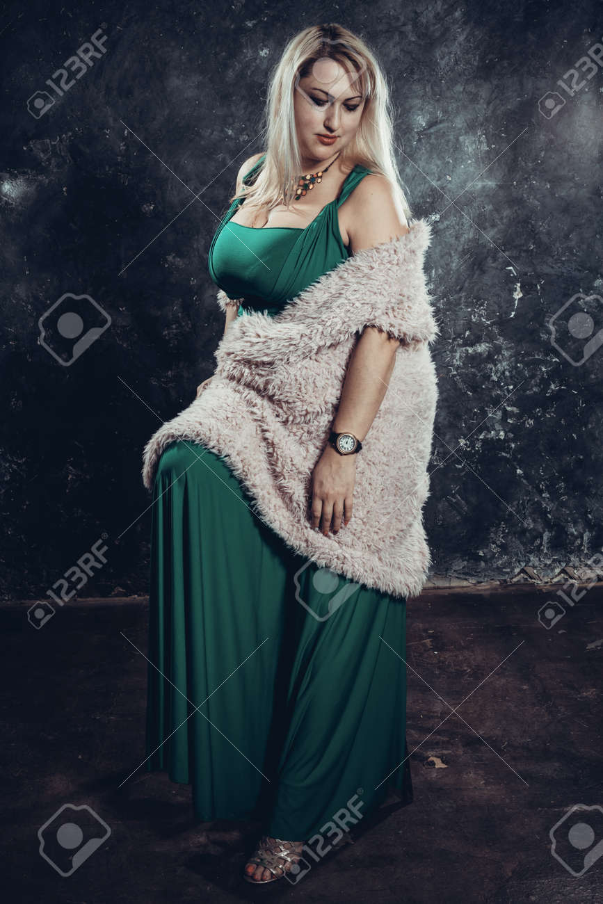 Attractive plump woman in green dress studio portrait. - 159144333