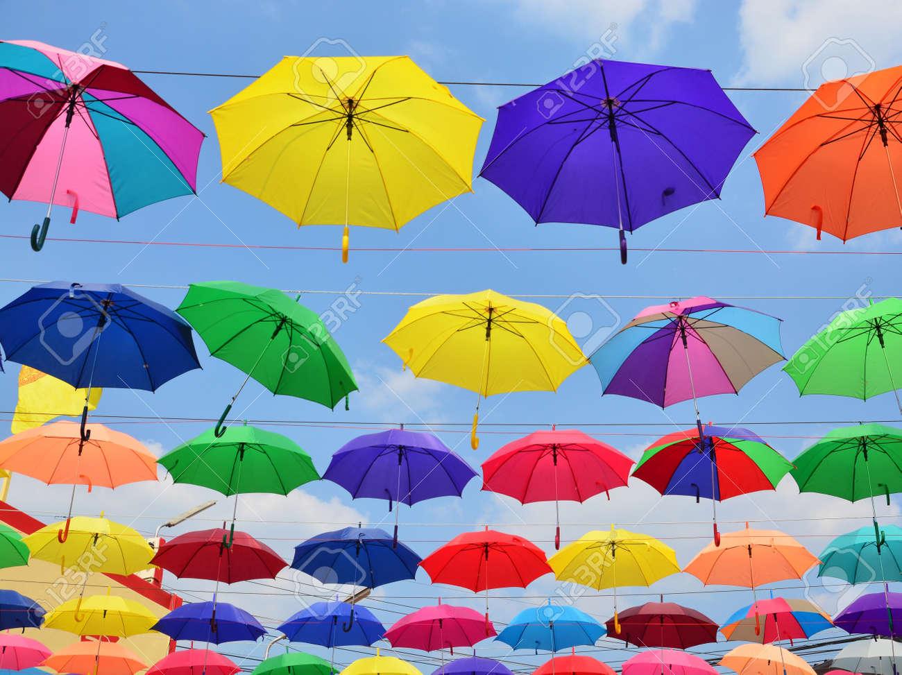 hombre como comprar precio especial para Fondo de paraguas de colores. Coloruful paraguas decoración de la calle  urbana. Colgando paraguas multicolores sobre cielo azul.