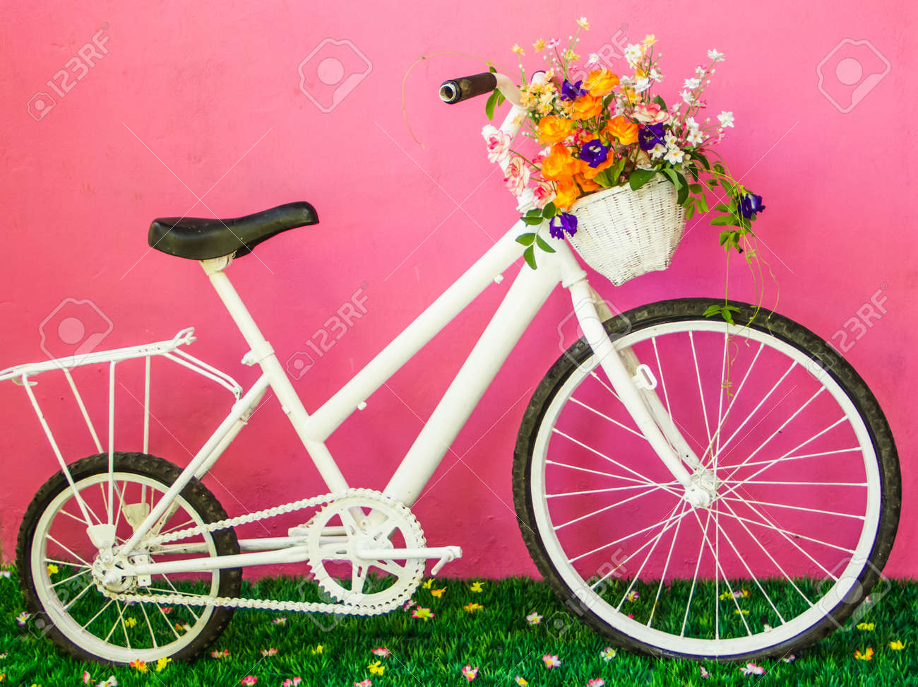 White vintage bicycle with flowers on the pink wall. - 23909693