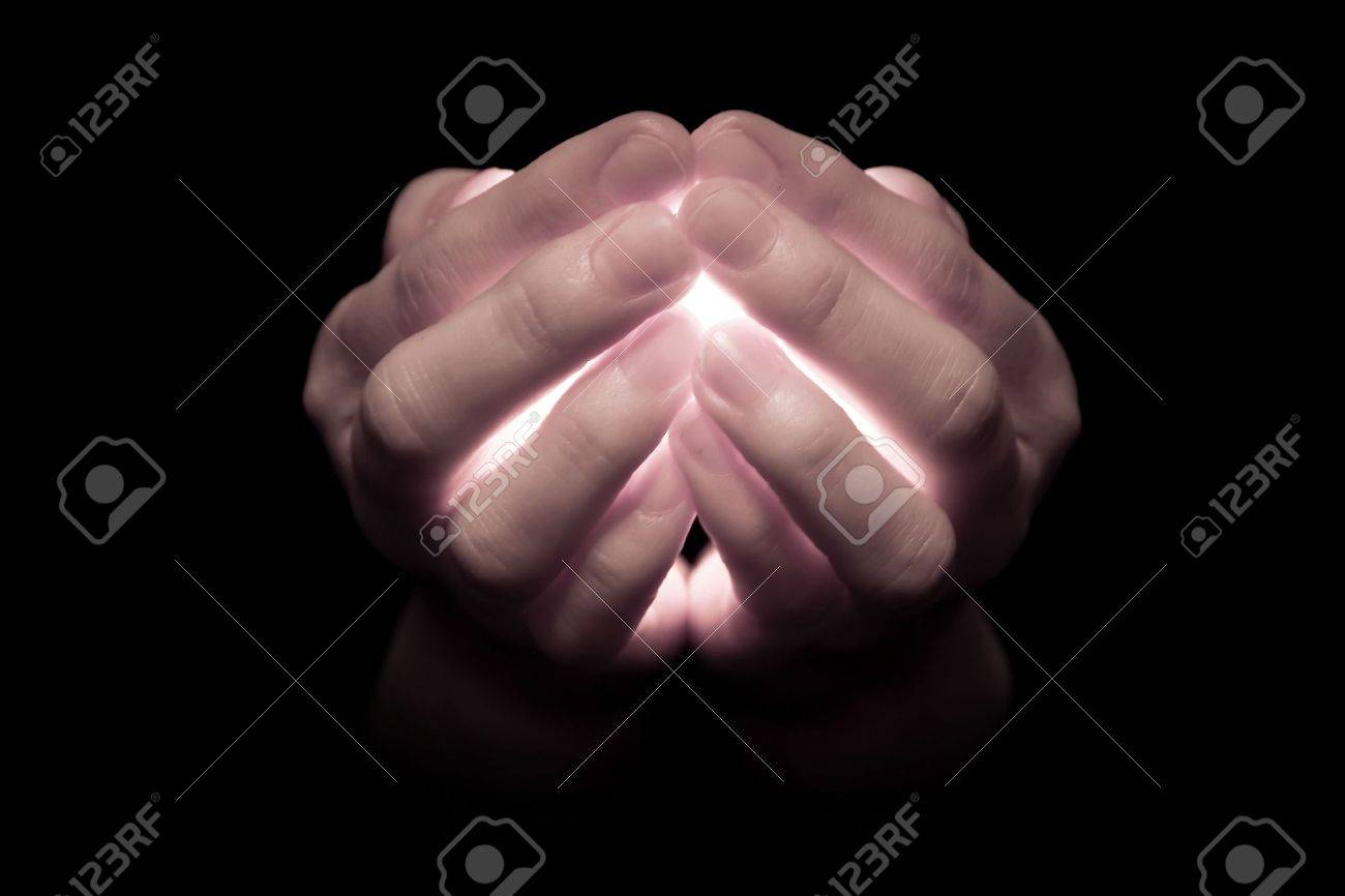 Hands holding a glowing candle, with light pouring through the fingers that appear translucent.  Muted tones. Stock Photo - 2286607