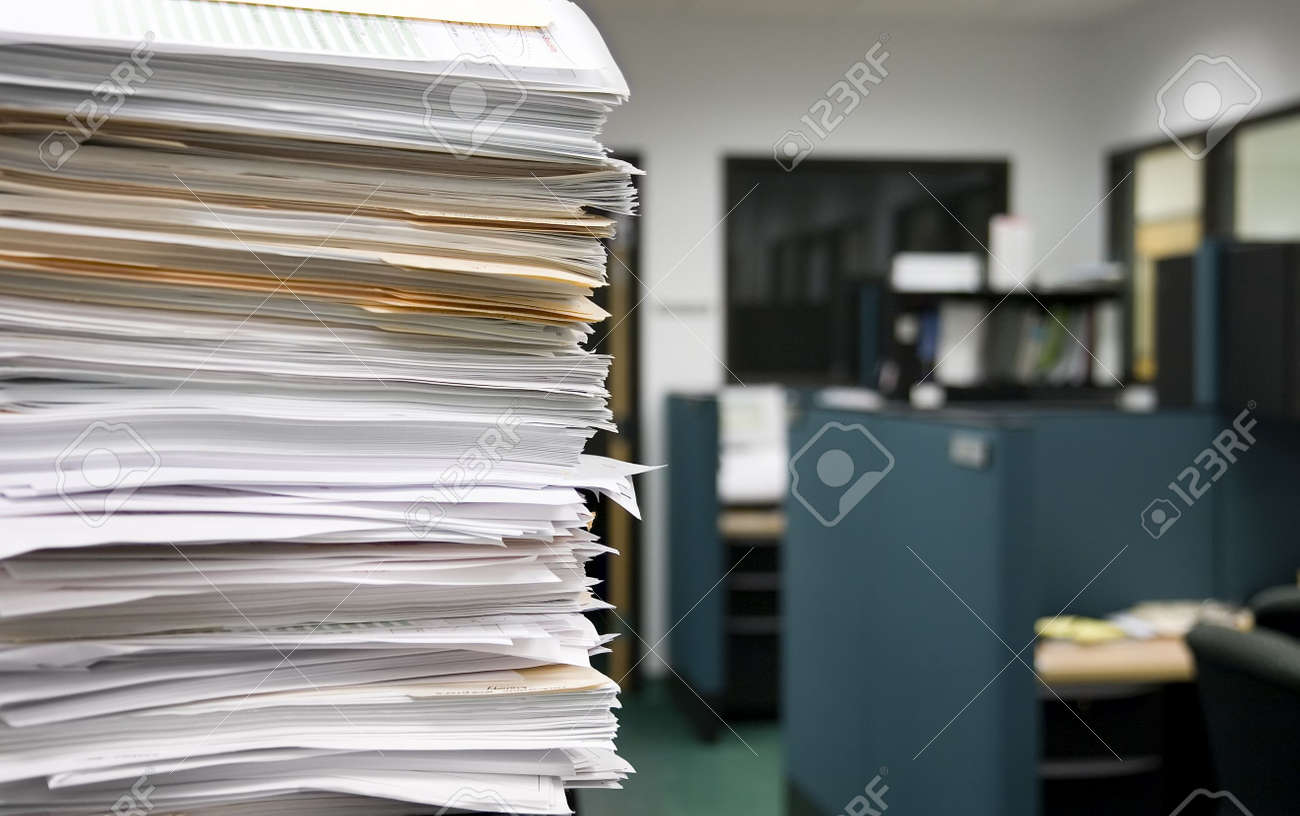 Pile Of Papers On A Background Of Office Cubicles Selective