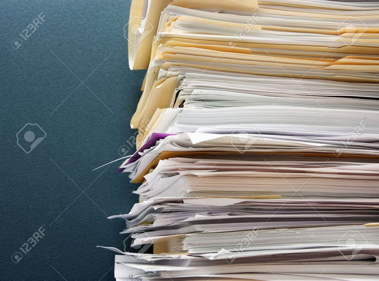 Pile of paperwork against a textured green cubicle wall - 2356215