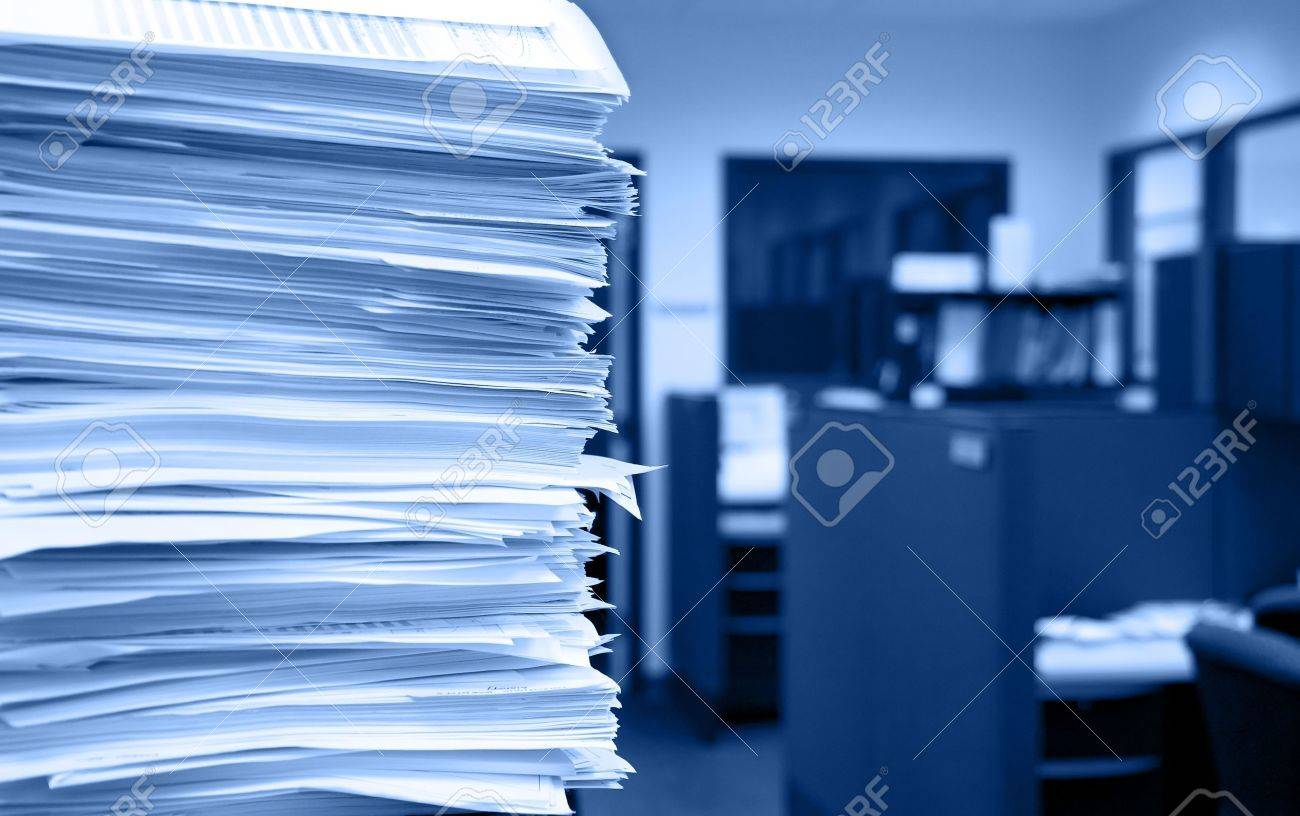 pile of papers on a background of office cubicles selective focus at the corner of - Office Cubicles