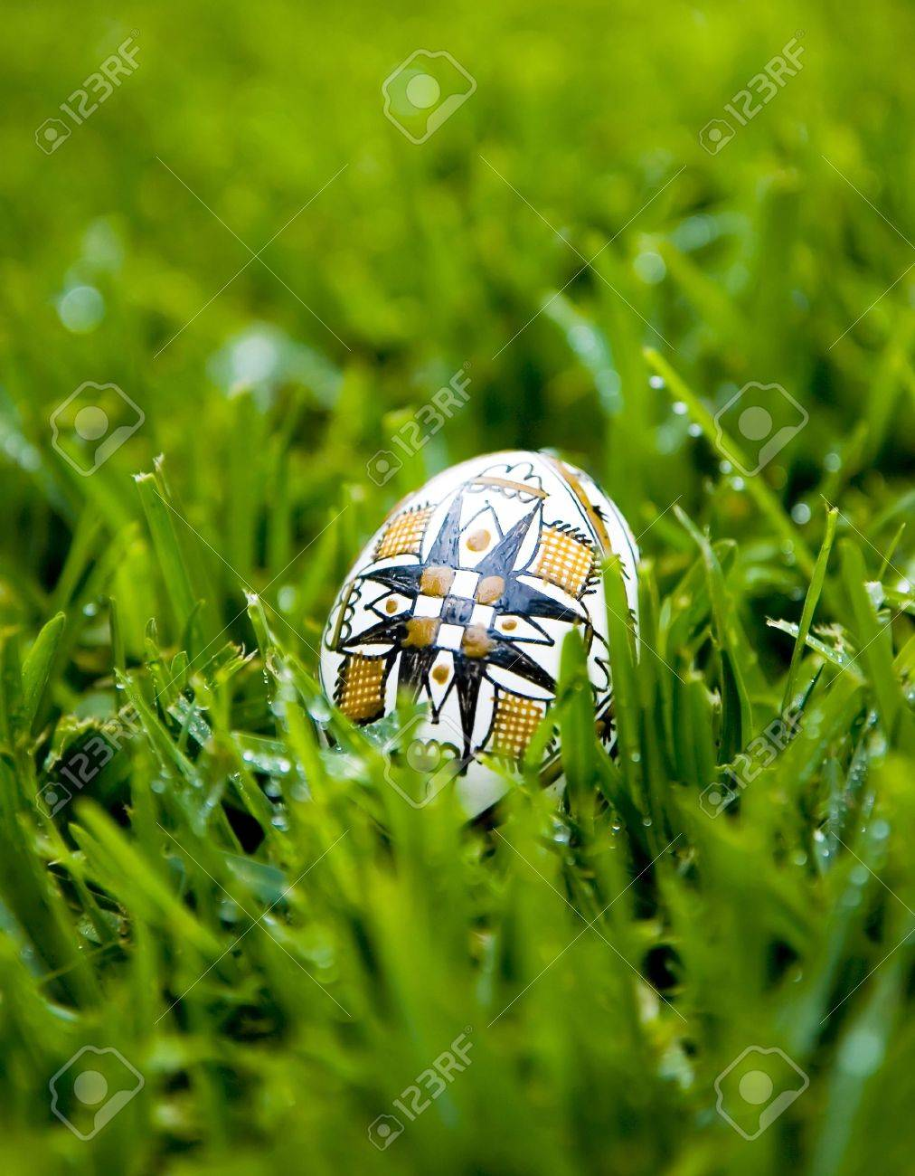 Traditional Easter Egg Painted With The Symbol Of Cross On Bright Green Grass