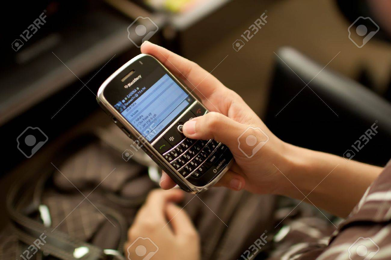 Woman using Blackberry Messenger to chat with her friend. - 14564862