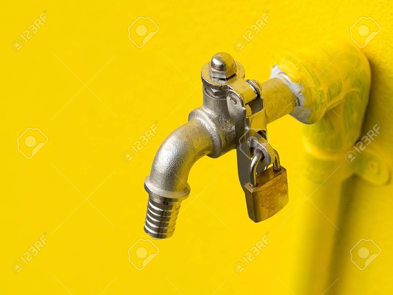 Yellow Faucet On Yellow Wall With Padlock Prevent Water Theft ...