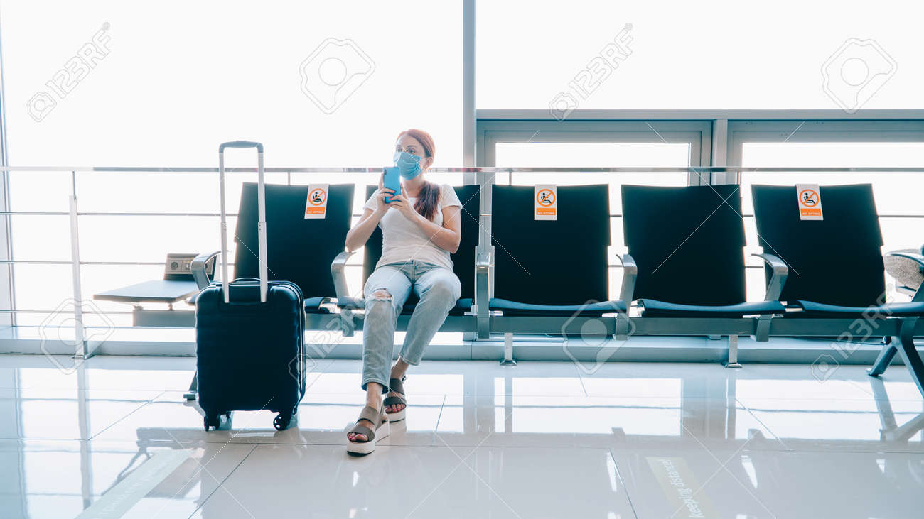 Safe travel. Woman traveler uses a smartphone while waiting for a flight at the airport terminal. Stickers on adjacent seats with the inscription - no sitting. - 166489071