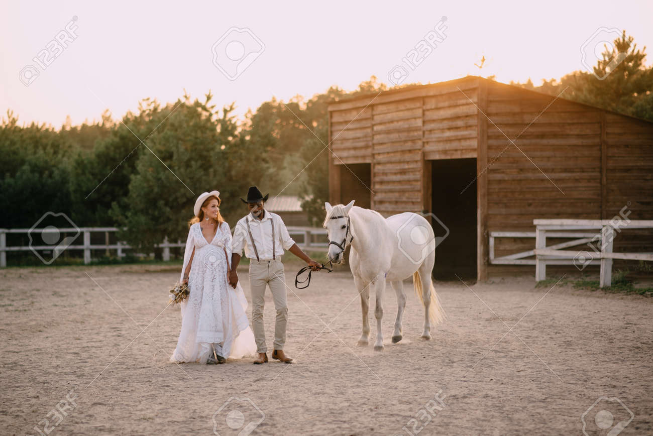Interracial couple expecting a baby. A pregnant woman in a white dress and her cowboy husband go with a horse to the ranch. Wide shot. - 167585852