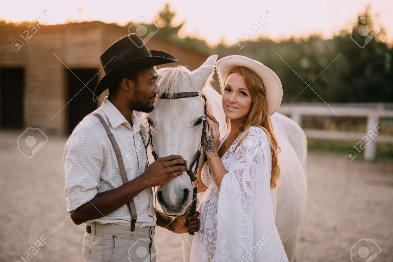 Interracial family. An African American man and his pregnant Caucasian wife stand near a horse on a ranch. Smiling woman looking at the camera. - 167585853