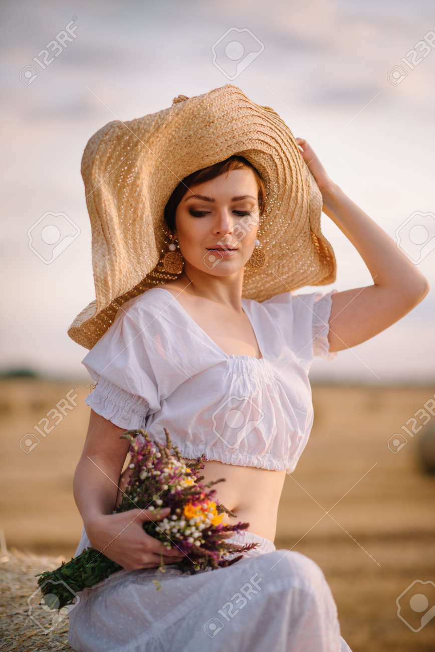 Summer mood. Portrait of a young beautiful woman in a hat in a field on a sunny day. Close up. - 170242571
