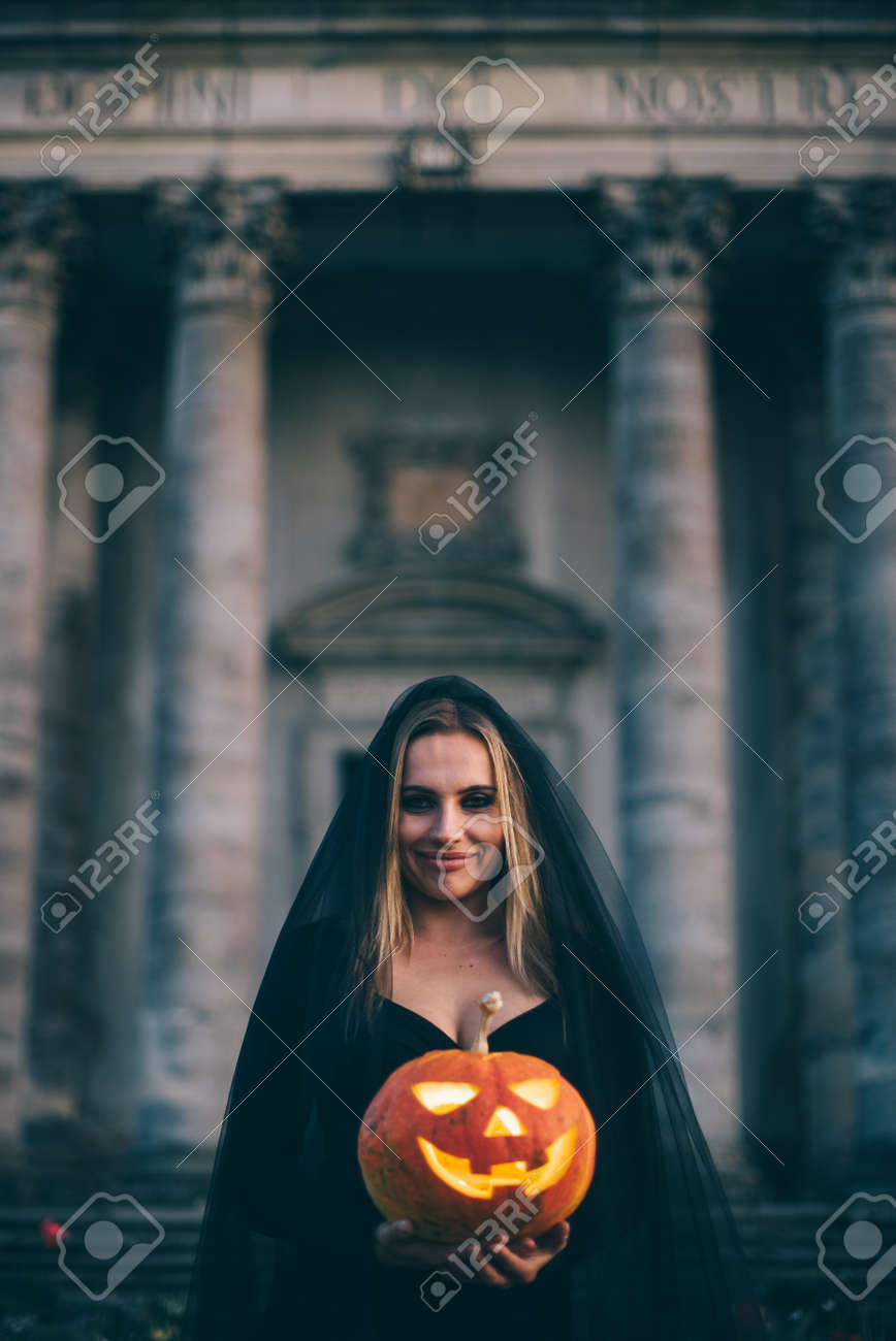 A witch woman holds a pumpkin with a scary face in her hands and looks at the camera at night. Close-up. - 171335880