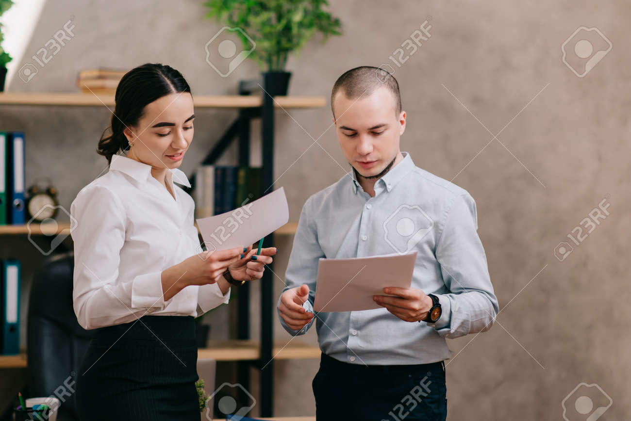 Work colleagues A man and a woman are discussing documents in the office. - 171315069
