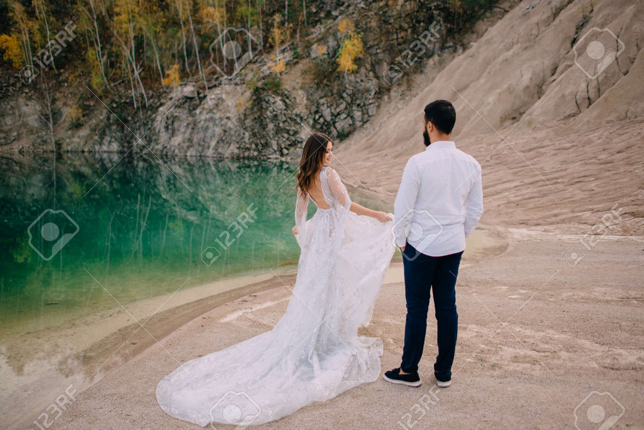 Newlyweds are standing near a beautiful lake. Middle Eastern groom and Caucasian bride hold hands on the beach. Back view. - 171315342