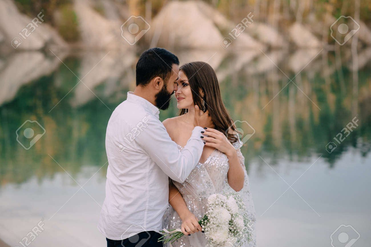Interracial relations. Middle Eastern groom and Caucasian bride hug against a beautiful lake. A man kisses a woman on the cheek. - 171314817