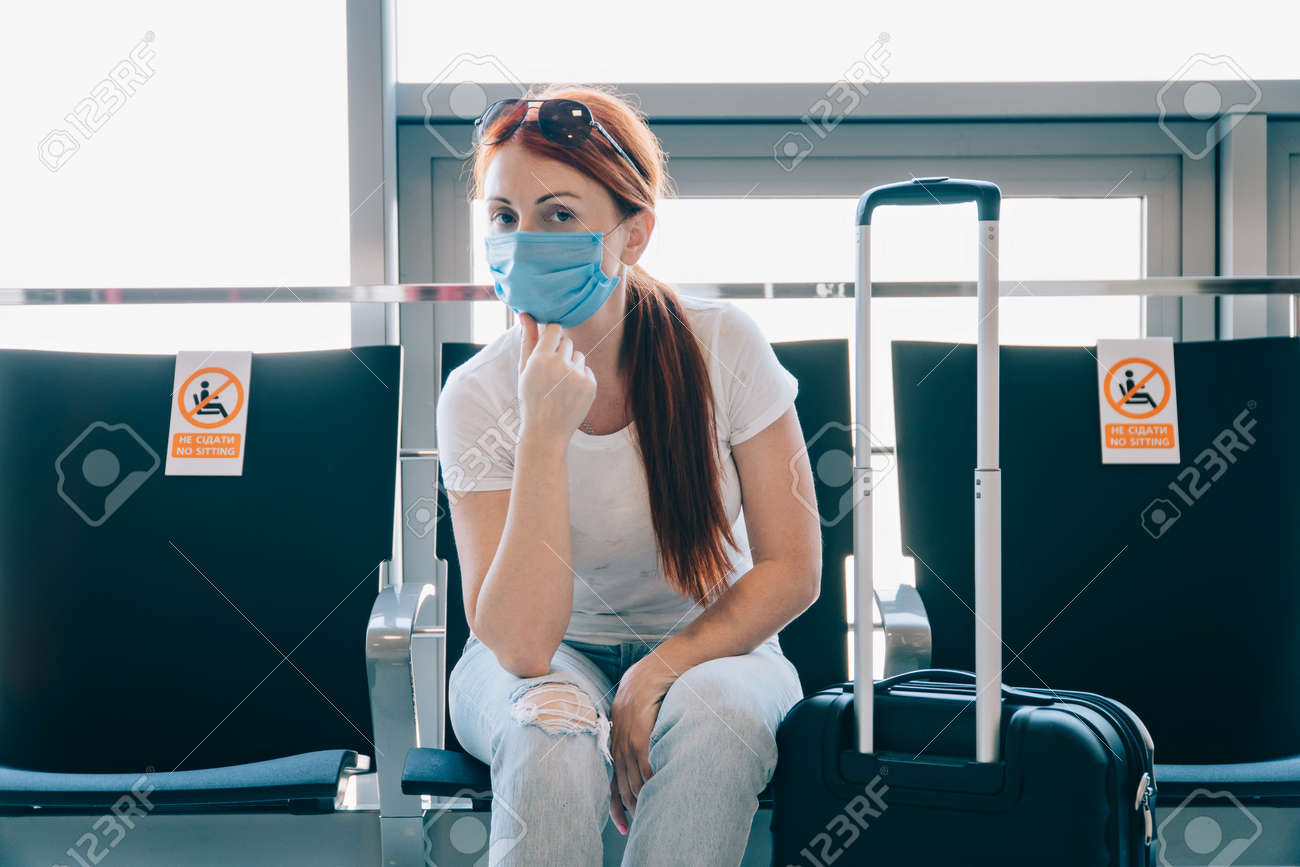 Safe travel. Young woman traveler in a medical mask is waiting for a flight at the airport terminal. Stickers on adjacent seats with the inscription - no sitting. - 171335882