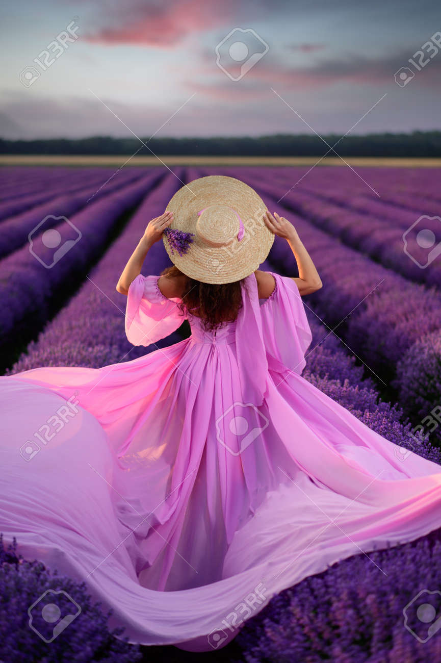 Woman in flying dress stands in blooming lavender field. Back view. Model holds straw hat with her hands. Beautiful sunset. - 171335884