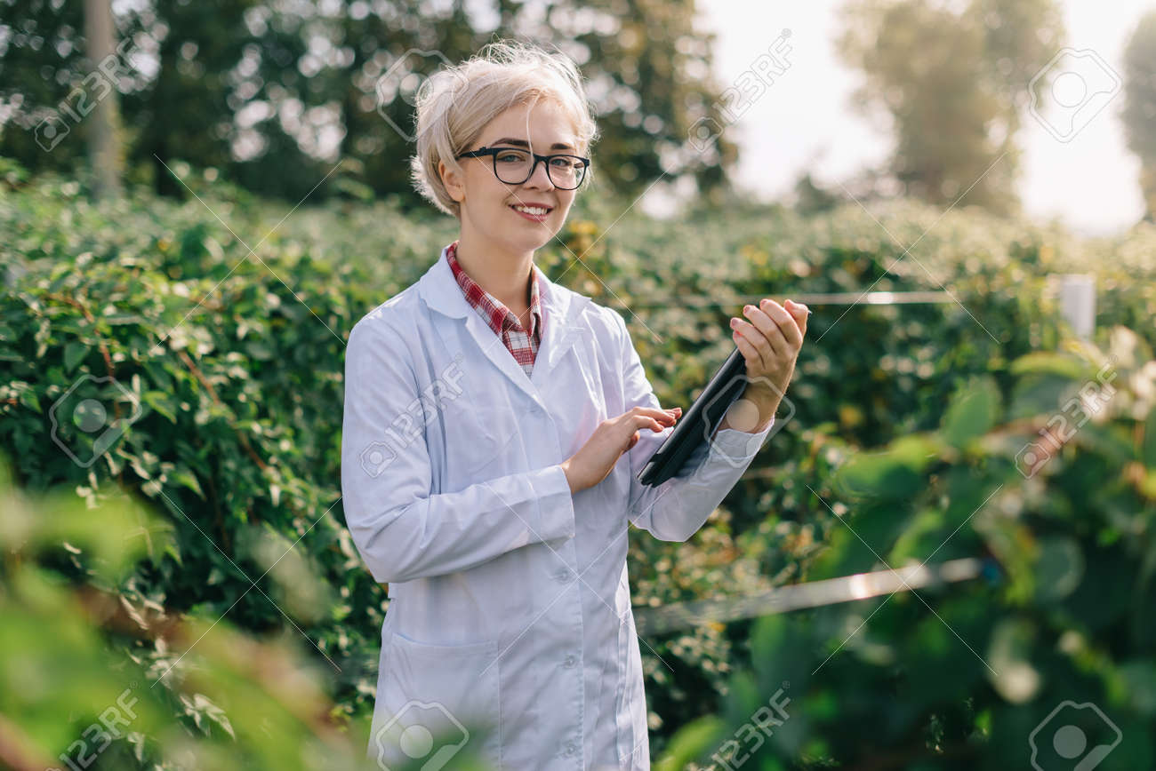 Agronomist at work. Portrait of young woman agronomist at plantation. Worker with tablet smiles and looks into camera. - 171366309