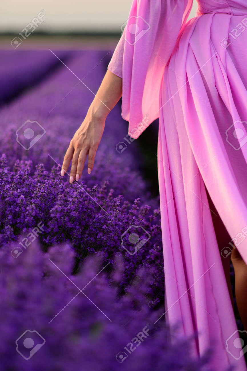 Young woman in beautiful pink dress touches lavender flowers with her fingers, cropped shot. Close-up of hand. - 171660832