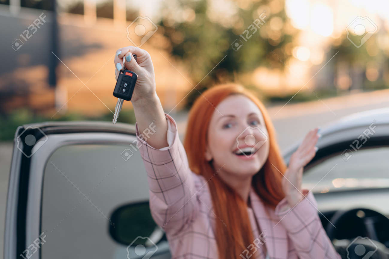 Woman won car. Happy winner holds keys in his hands while standing near car. Selective focus. - 171476959