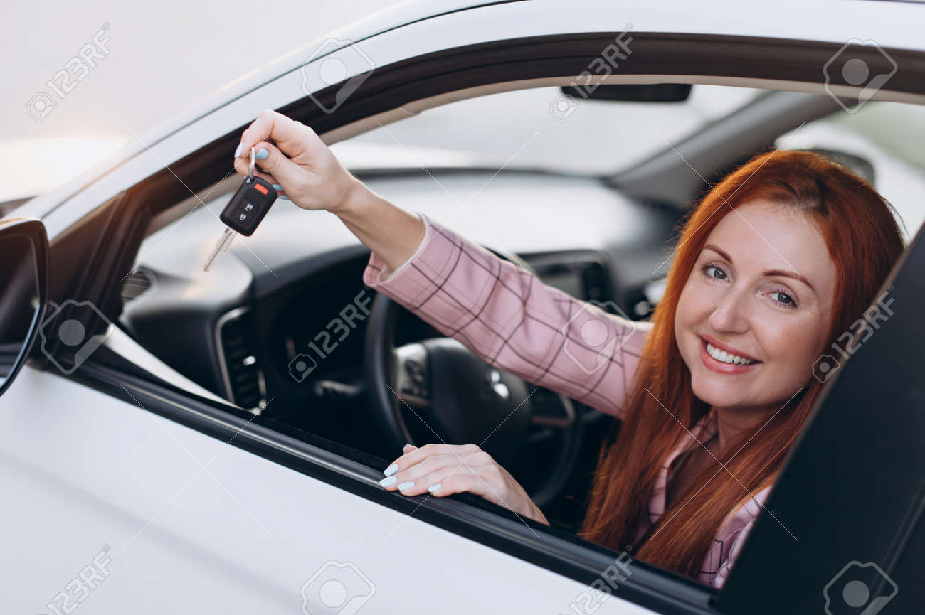 Happy young woman driver sits behind wheel of car and shows keys. - 171477489