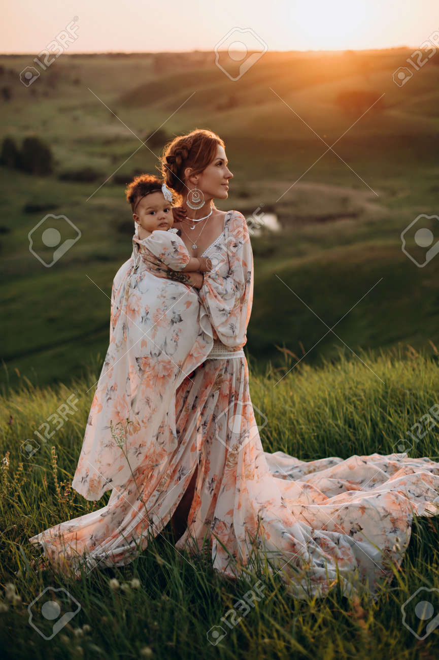 Interracial family. Young caucasian woman holding an african baby outdoors. Full-length portrait. - 171482351
