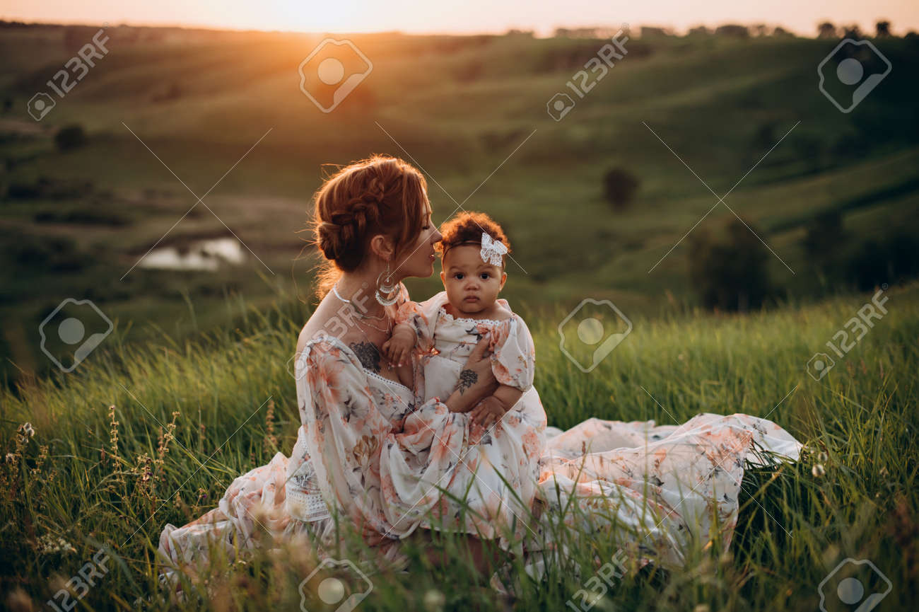 Interracial family. Young caucasian woman holding an african baby outdoors. Mom and one-year-old daughter are sitting on grass. - 171482401