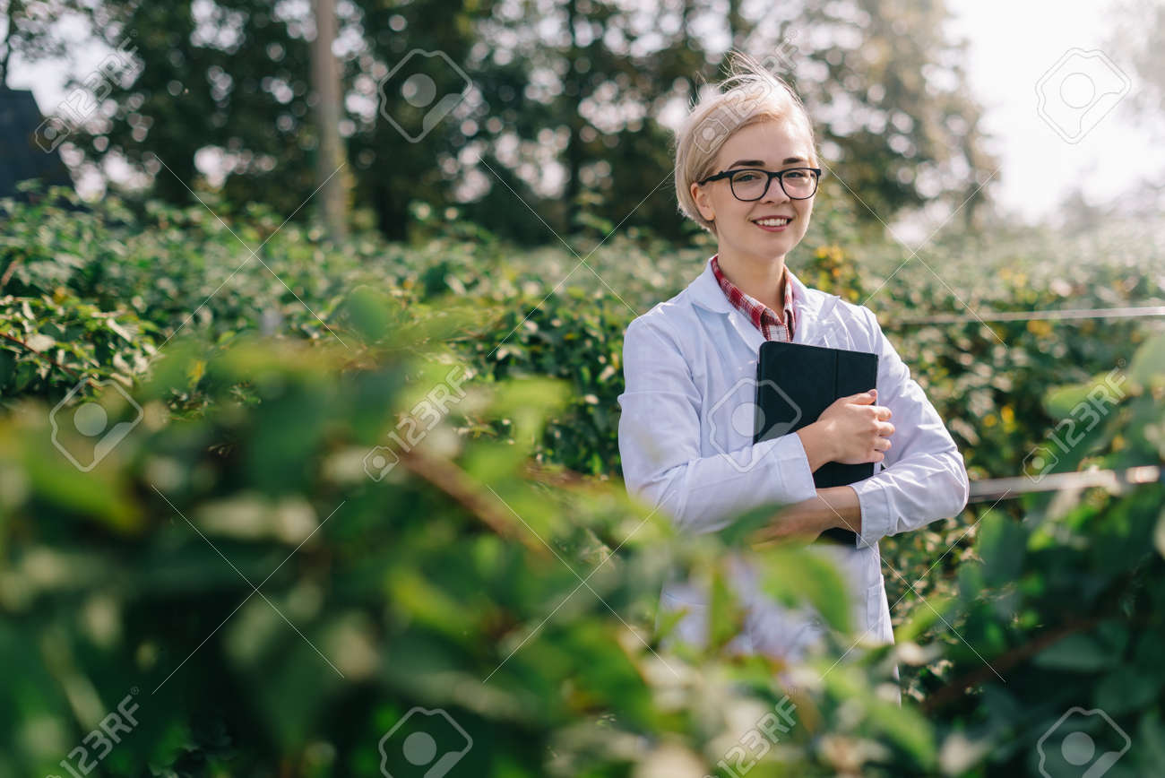 Agronomist at work. Portrait of young woman agronomist at plantation. Worker with tablet smiles and looks into camera. - 171483235