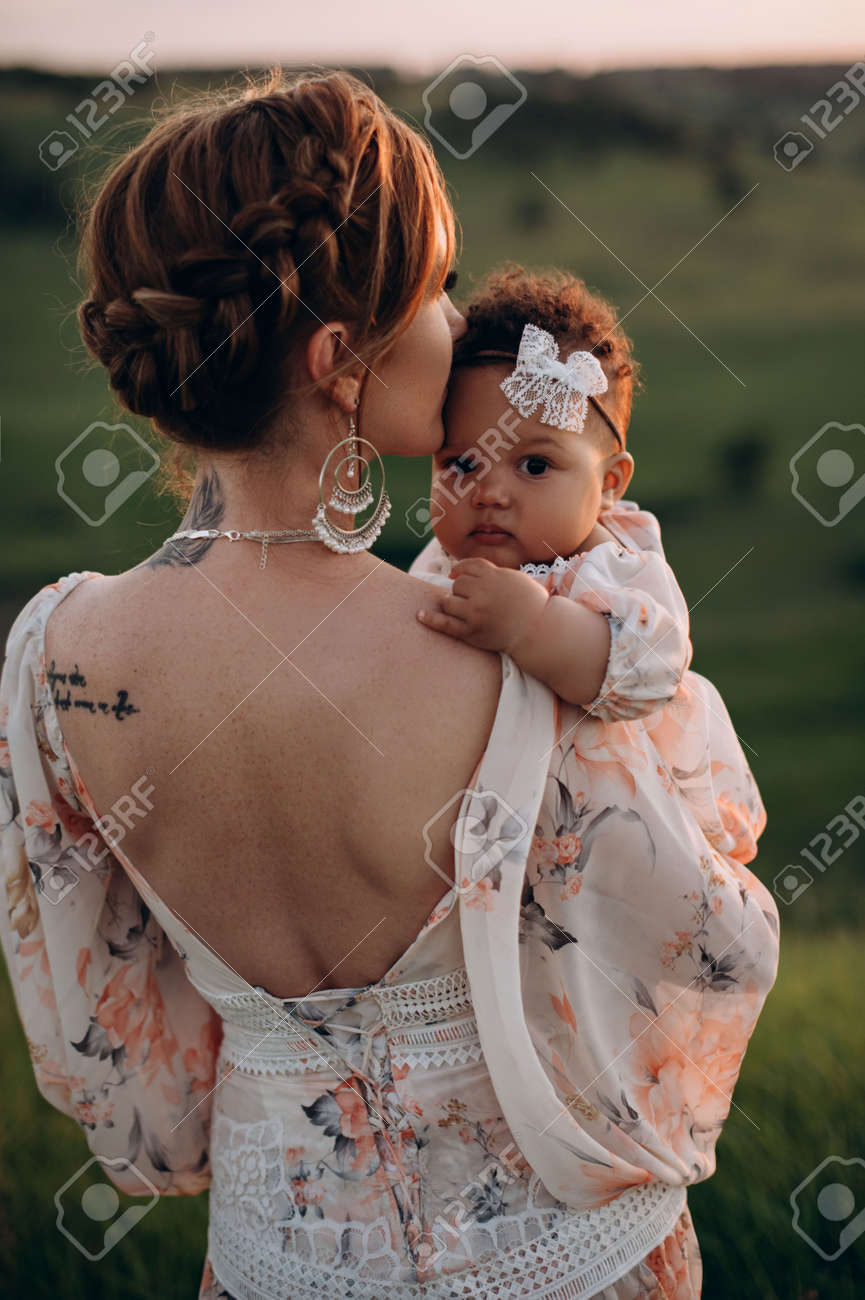 Interracial family. Young caucasian woman holding an african baby outdoors. Little girl looking at camera. Close up. - 173391461