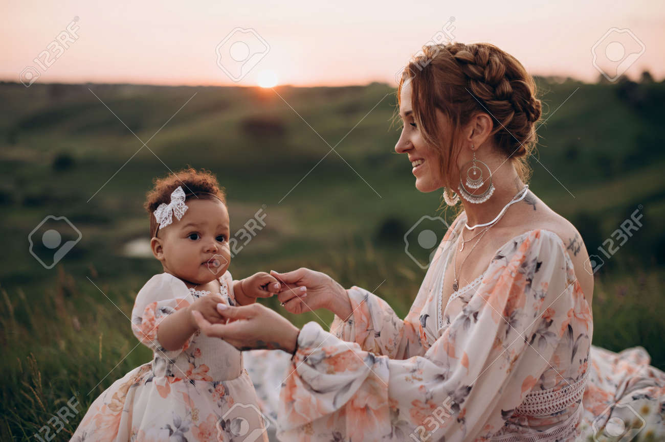 Interracial family. Young caucasian woman holding an african baby outdoors. Mom and one-year-old daughter are sitting on grass. - 172585775