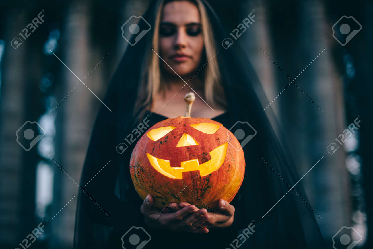 A young woman witch in black clothes holds a pumpkin with a terrible face in her hands and looks ominously into the camera. Close-up portrait. - 172586106