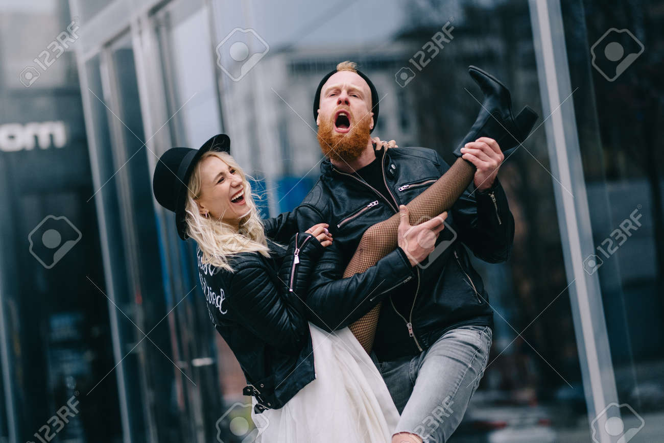 Crazy newlyweds in city. Groom pretends to sing and holds brides leg like guitar. - 173391493