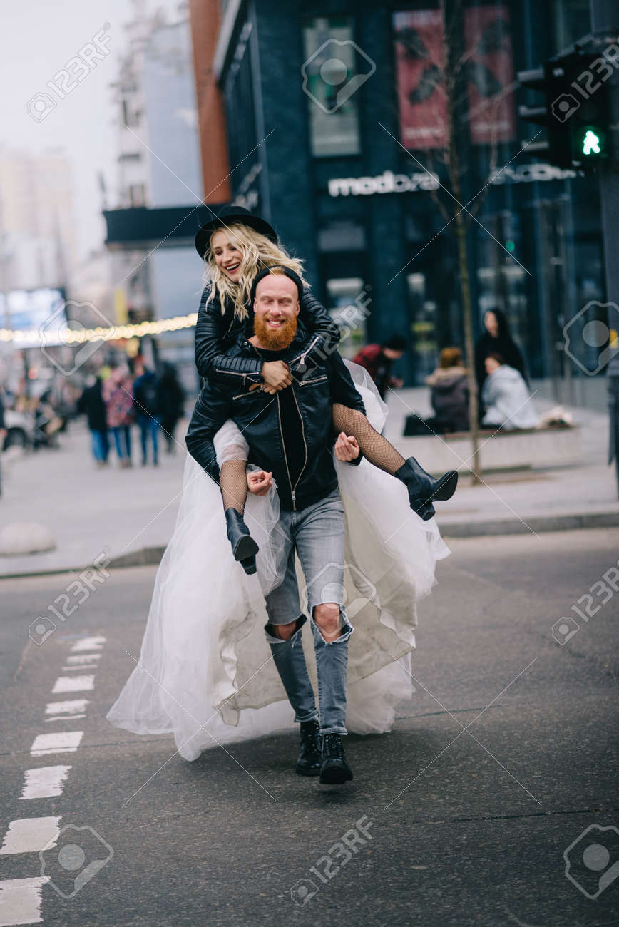 Crazy newlyweds in city. Bride rides her groom on street. New York, USA. - 173469845