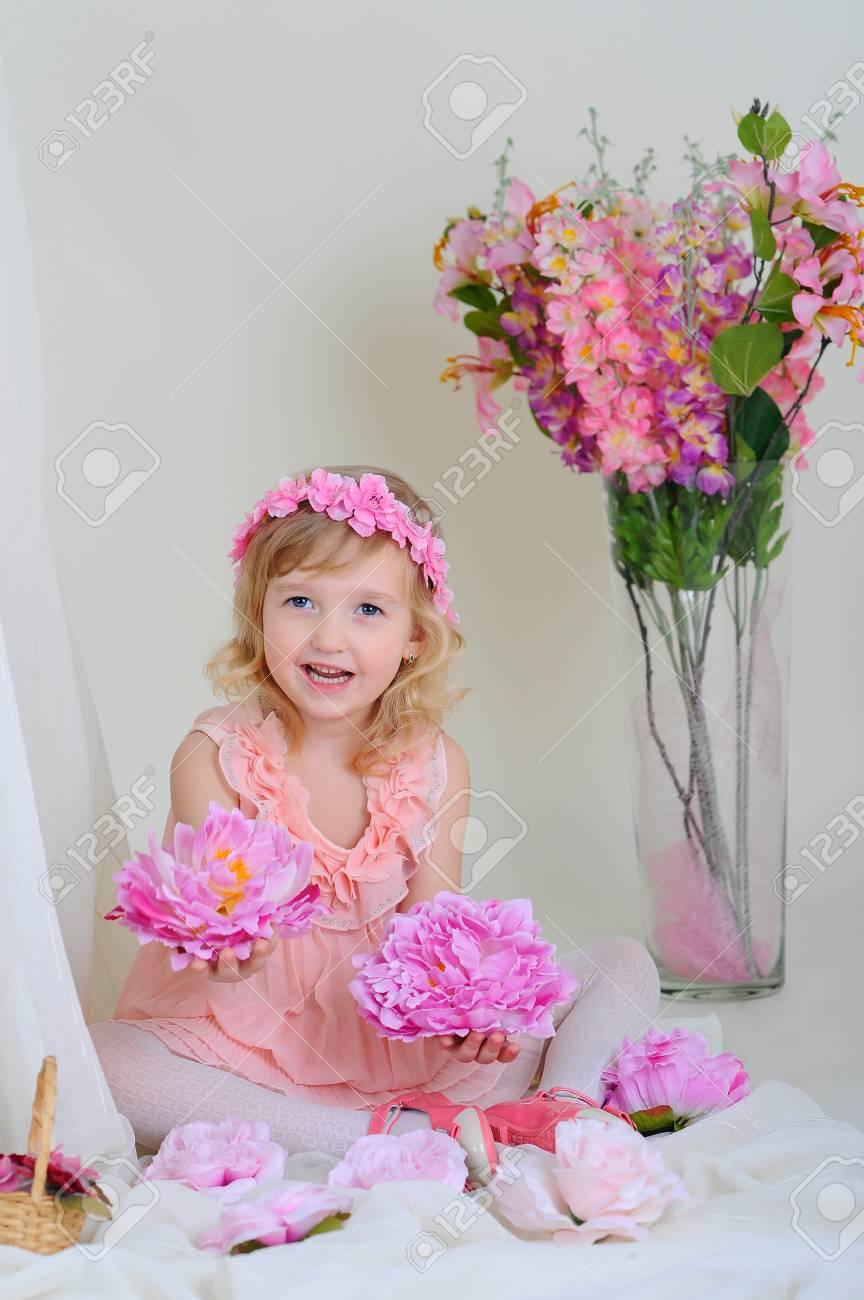 Niña En Un Vestido De Color Rosa Cerca De Los Ramos De Flores Sentado En Las Flores De Suelo Sosteniendo