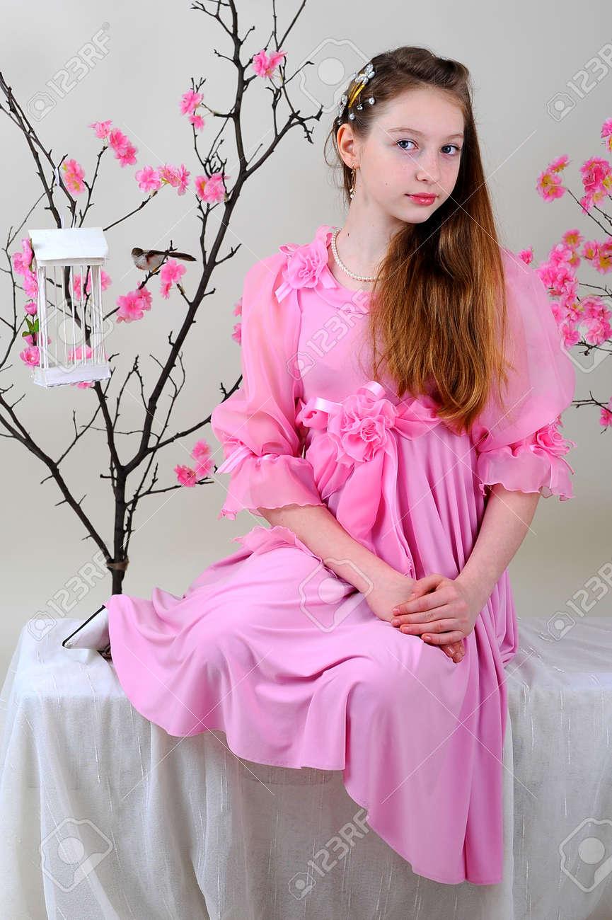 Niña En Un Vestido Rosa Se Sienta Pensativo Cerca De Florecimiento ...