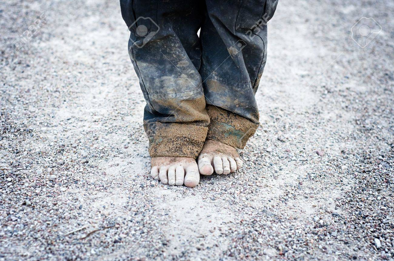 dirty and child's feet on gravel. Poverty concept - 9613691