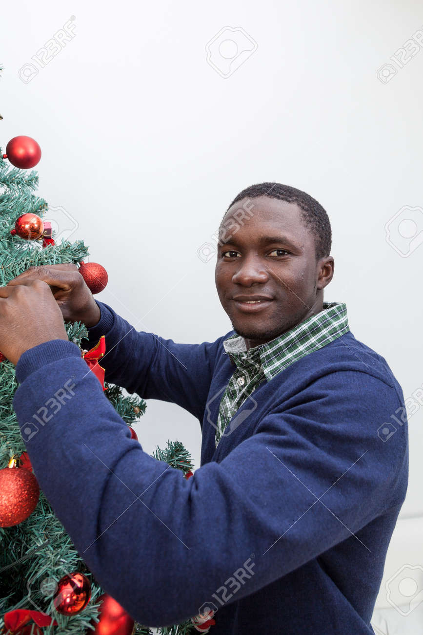 Black People Decorating For Christmas black man decorating the christmas tree stock photo, picture and