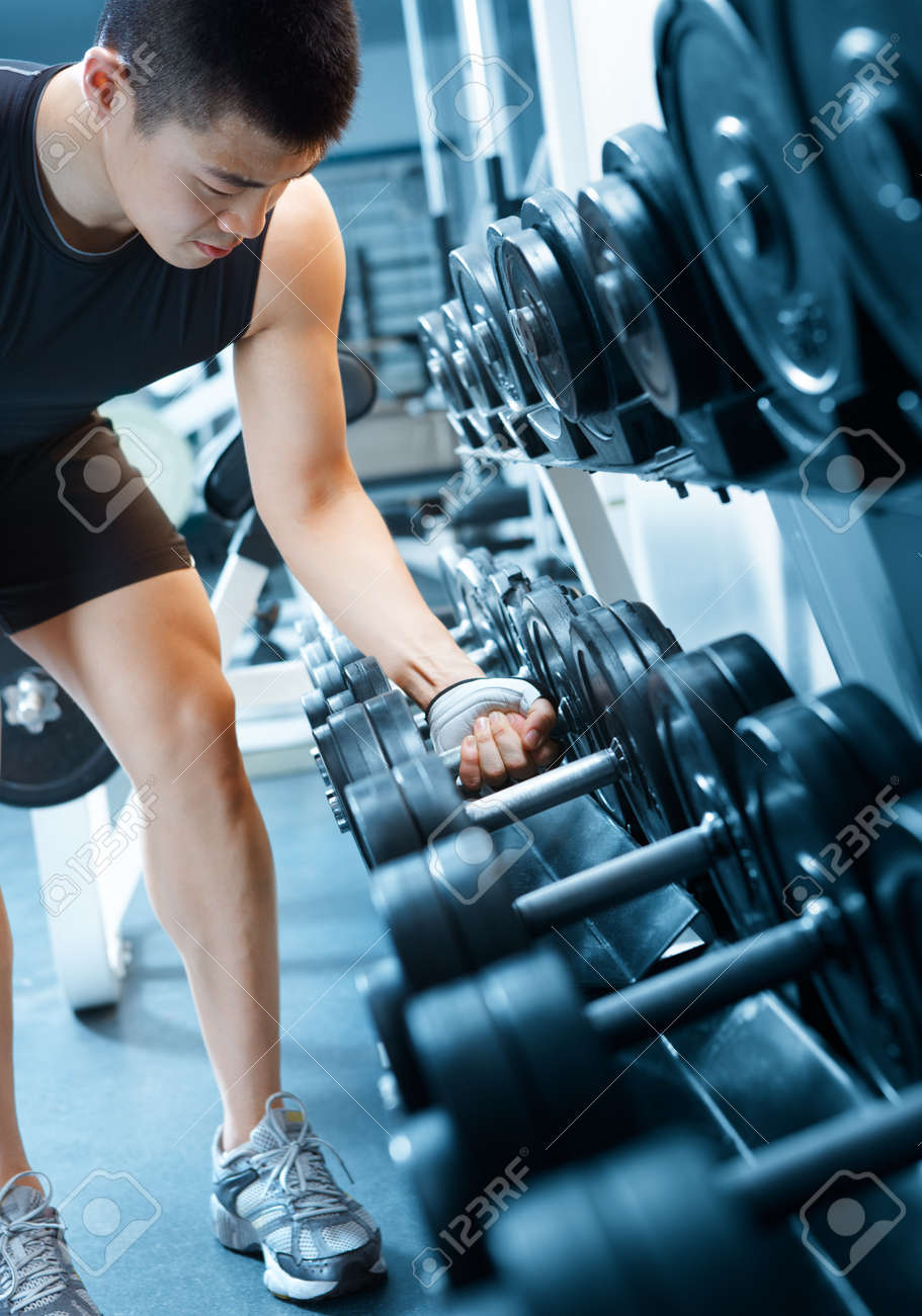 asian man choosing dumbbell in health club Stock Photo - 9833257